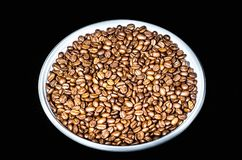 Coffee beans on a round plate close up. Isolated on black background royalty free stock photo