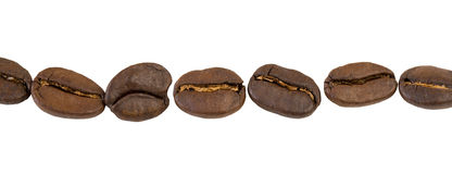 Coffee beans in a row, isolated on white background close up. Coffee beans in a line, isolated on white background close up Stock Photo