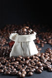 Coffee beans in a sack. With a lot of beans around it stock photo
