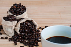 Coffee beans sack and coffee cup. Over wooden background Royalty Free Stock Image