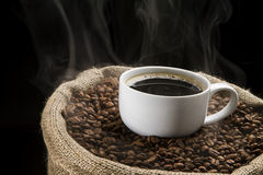 Coffee beans in the sack with cup of coffee. Sack full of still hot, freshly roasted coffee beans with the mug in the middle Royalty Free Stock Image