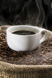 Coffee beans in the sack with cup of coffee. Royalty Free Stock Photos