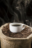 Coffee beans in the sack with cup of coffee. Royalty Free Stock Photo