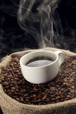 Coffee beans in the sack with cup of coffee. Stock Image
