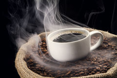 Coffee beans in the sack with cup of coffee. Royalty Free Stock Images