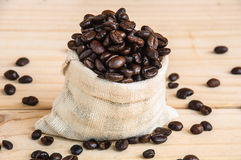 Coffee beans sack. Over wooden background royalty free stock image