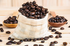 Coffee beans sack. Over wooden background Royalty Free Stock Photo