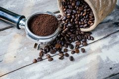 Coffee beans in sack and portafilter on old white wooden table royalty free stock photo