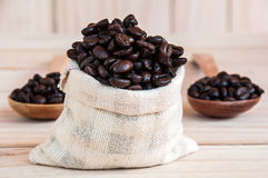 Coffee beans sack. With spoon over wooden background royalty free stock photo