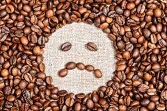 Coffee beans sad smile on burlap. Background Royalty Free Stock Photography