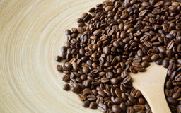 Coffee beans scattered on beige bamboo plate, closeup. With copy space. Arabica seeds heap and big wooden spoon pouring in it, soft color toning Royalty Free Stock Photo