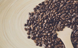 Coffee beans scattered on beige bamboo plate, closeup. With copy space. Arabica seeds heap and big wooden spoon pouring in it, soft color toning royalty free stock photography