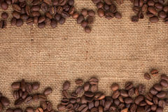 Coffee beans scattered on burlap Royalty Free Stock Images