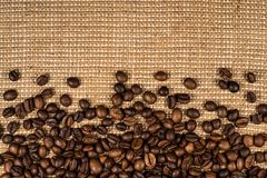 Coffee beans scattered on burlap. Can be used as background Stock Images