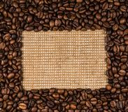 Coffee beans scattered on burlap. Can be used as background Stock Photo