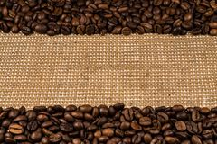 Coffee beans scattered on burlap Royalty Free Stock Photos