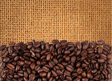Coffee beans scattered on burlap can be used. As background Royalty Free Stock Image