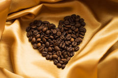 Coffee beans scattered on  fabric in the form of heart Stock Photo