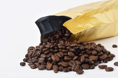 Coffee beans. Scattered from the gold bag  on wihite background Stock Photos