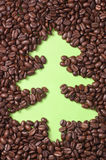 Coffee beans scattered on green paper with drawn christmas tree Royalty Free Stock Images