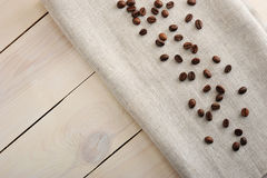 Coffee beans scattered on a linen cloth Stock Images