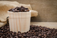 Coffee beans set up on wooden cask and rustic background.  Stock Photo