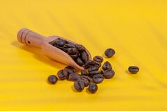 Coffee beans  with shadows from a palm tree in a coffee spoon scattered on a yellow background