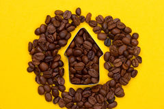 Coffee beans in the shape of arrow. On yellow background Stock Photos
