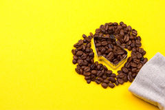 Coffee beans in the shape of arrow. On yellow background Stock Photography