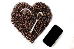 Coffee beans in the shape of a big heart with mug. Spoon & cell phone Top view Isolated  in white background Stock Photo