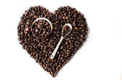 Coffee beans in the shape of a big heart with mug. Top view cup Isolated  in white background Stock Photo