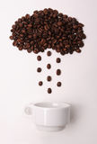 Coffee beans in shape of cloud pouring rain in a white cup on white background Stock Photo