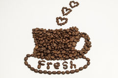 Coffee Beans in the shape of a cup and saucer. With heart steam and fresh written in the saucer Royalty Free Stock Photo