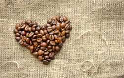 Coffee beans in the shape of a heart on the burlap. Heart with roasted coffee beans on the burlap background Stock Photo