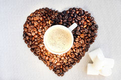 Coffee beans in the shape of a heart and a cup of freshly brewed coffee. Background from coffee Valentine`s Day. Royalty Free Stock Images
