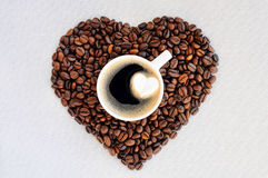 Coffee beans in the shape of a heart and a cup of freshly brewed coffee. Background from coffee Valentine`s Day. Royalty Free Stock Image