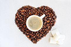 Coffee beans in the shape of a heart and a cup of freshly brewed coffee. Background from coffee Valentine`s Day. Stock Photos