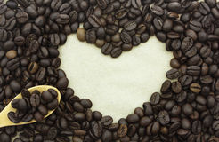 Coffee beans in shape of heart on paper background. Stock Photo