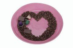 Coffee beans in shape of a heart with pieces of chocolate and coffee capsules isolated on white background with clipping path. stock photo