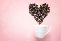 Coffee beans in shape of heart and white cup on pink background. Royalty Free Stock Images