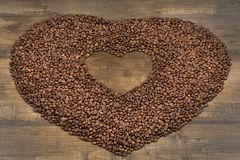 Heart of coffee beans on a wooden surface. Coffee beans in the shape of heart on a wooden background with place for text. Postcard, blank, template for St Royalty Free Stock Photography