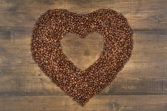 Heart of coffee beans on a wooden surface. Coffee beans in the shape of heart on a wooden background with place for text. Postcard, blank, template for St Royalty Free Stock Photo