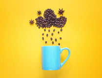 Coffee beans in shape of rainy cloud with anise stars and blue m. Ug on yellow Stock Image