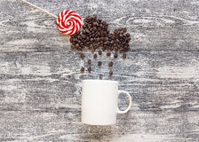Coffee beans in shape of rainy cloud with lollipop and white cup Royalty Free Stock Photo