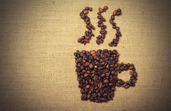 Coffee beans shaped as cup over a jute cloth. Background royalty free stock photos