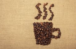 Coffee beans shaped as cup over a jute cloth stock photo