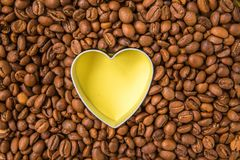 Coffee beans shaped heart top view. Yellow heart between raw cof. Fee Stock Images