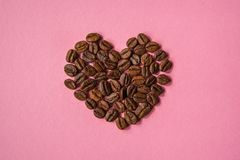 Coffee beans shaped hearts on a pink background. Love coffee con Royalty Free Stock Photography