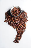 Coffee beans shaped like south america. And black cups stock photos