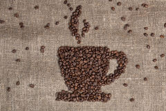 Coffee beans shaping cup on burlap. Roasted coffee beans shaping cup on burlap Stock Images